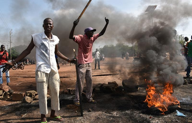 People shout as they stand next to a tyre set on fire during a protest against a regional proposal to end the crisis in Burkina Faso, in Ouagadougou on September 21, 2015 (AFP Photo/Sia Kambou)
