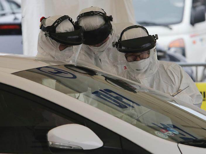 """Medical staff wearing protective suits take samples from a driver with symptoms of the coronavirus at a """"drive-thru"""" virus test facility in Goyang, South Korea, March 1, 2020."""