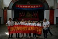 This picture taken during a government-organised media tour shows tourists wearing commemorative T-shirts and unfurling a banner in Yan'an