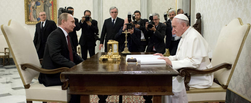 RETRANSMITTING TO PROVIDE ALTERNATIVE CROP OF VAT104. In this photo provided by the Vatican newspaper L'Osservatore Romano, Pope Francis, right, and Russian President Vladimir Putin sit at a table on the occasion of their private audience at the Vatican, Monday, Nov. 25, 2013. Putin and Francis met privately for 35 minutes Monday evening in the pope's private library. (AP Photo/L'Osservatore Romano, ho)