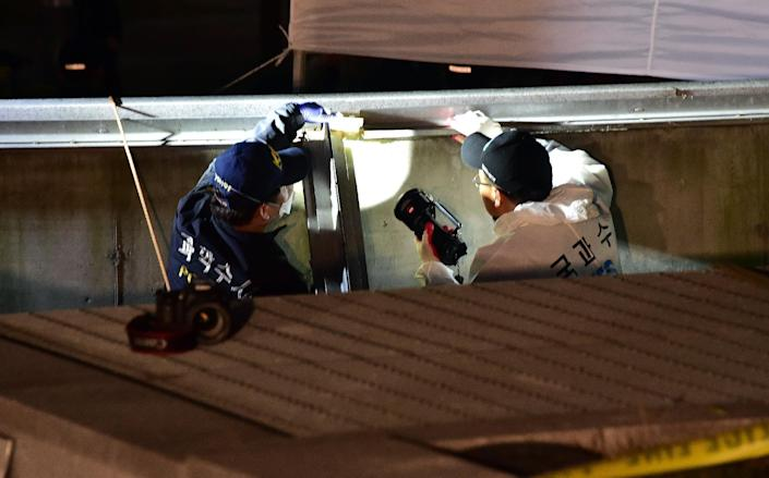 South Korean forensic offiers check a broken ventilation grate after concert goers fell through it into an underground parking area in Seongnam on October 17, 2014 (AFP Photo/Jung Yeon-Je)
