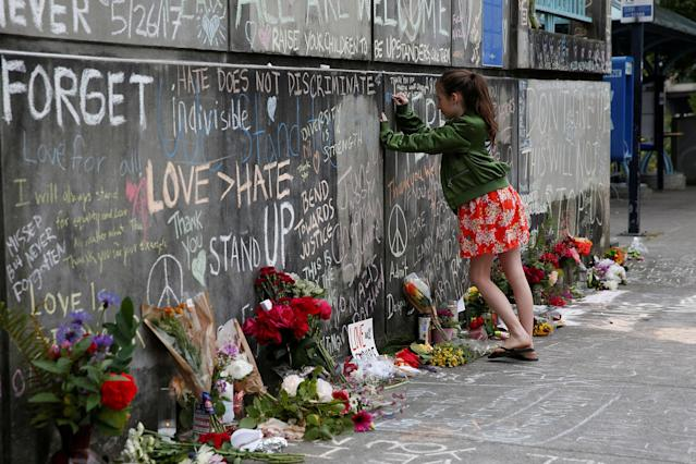 <p>A girl leaves a message at a makeshift memorial for two men who were killed on a commuter train while trying to stop another man from harassing two young women who appeared to be Muslim, in Portland, Ore., May 29, 2017. (Terray Sylvester/Reuters) </p>