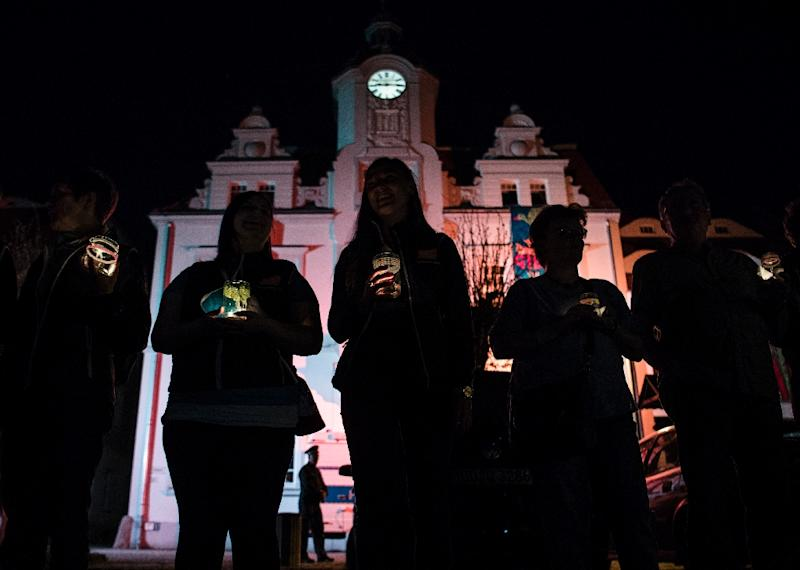 """Residents hold a candle-light vigil in Ostritz' main square during a """"Peace Festival"""" held to coincide with the Shield and Sword neo-nazi festival, in the eastern German town on April 20, 2018 (AFP Photo/John MACDOUGALL)"""