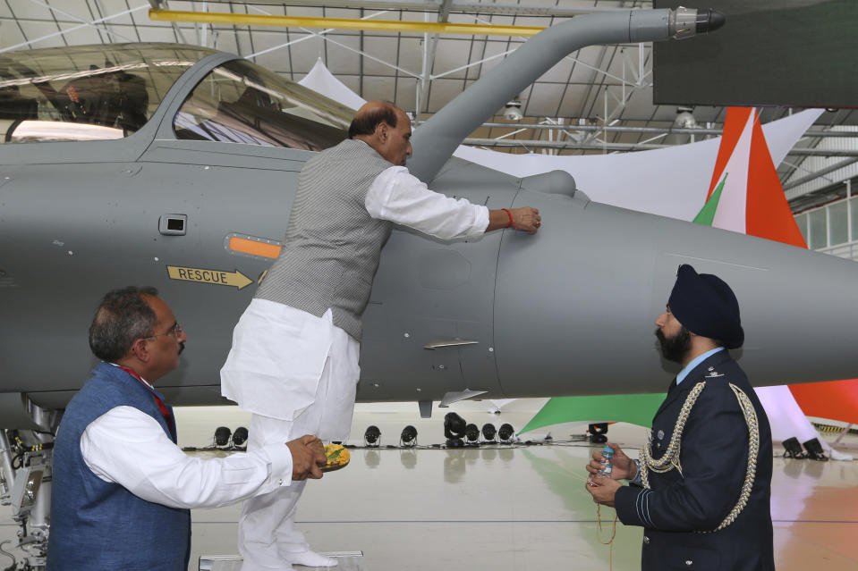 FILE- In this Oct. 8, 2019, file photo, Indian Defense Minister Rajnath Singh writes onto a Rafale jet fighter as a ritual gesture during an handover ceremony at the Dassault Aviation plant in Merignac, near Bordeaux, southwestern France. In India, the relationship between faith and science is complicated. Seeking comfort in the certainty of the past, Indians are tuning into re-runs of popular Hindu religious dramas, drawing on shared experiences of old times when most questions had answers. (AP Photo/Bob Edme, File)