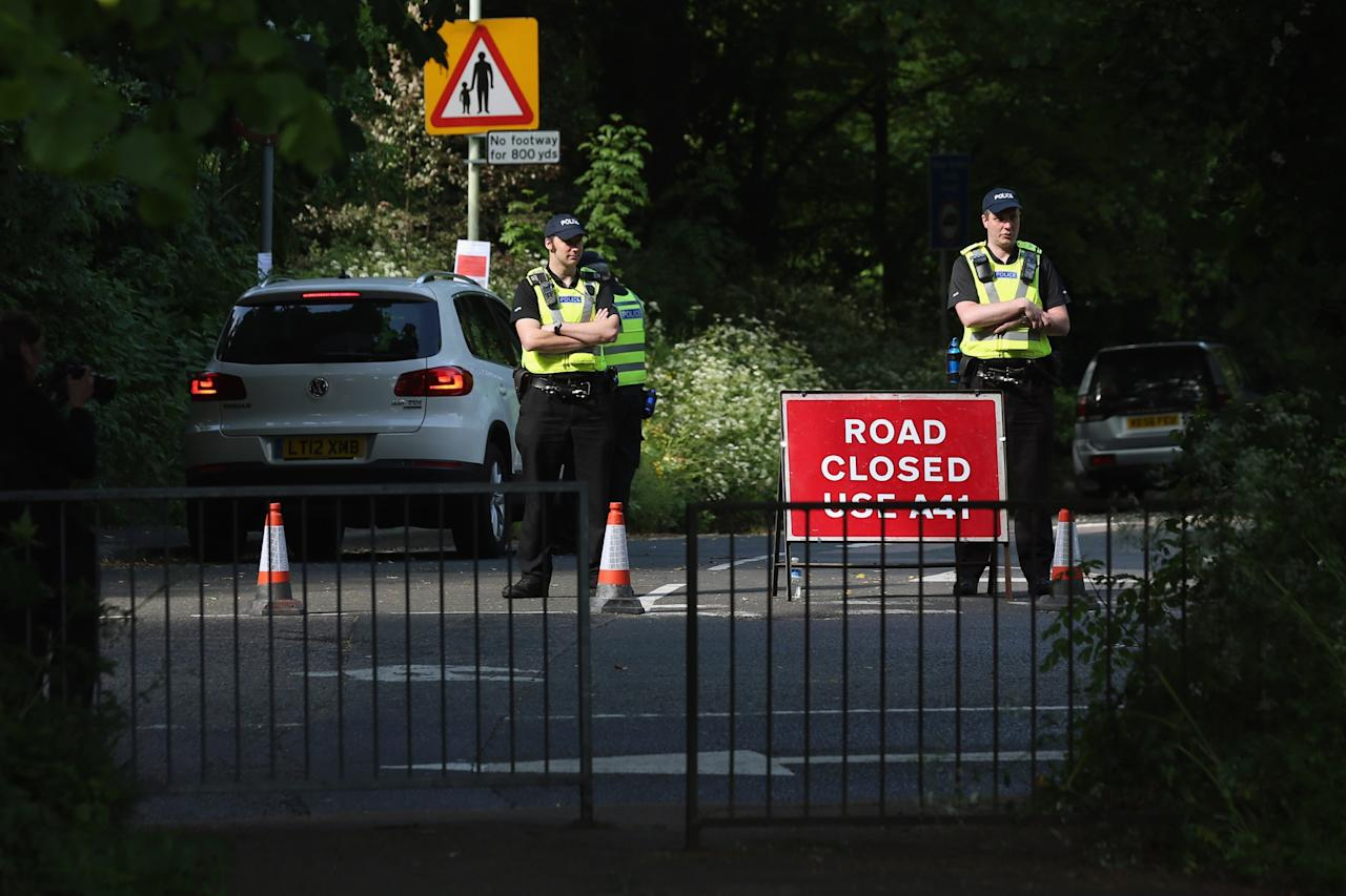 WATFORD, ENGLAND - JUNE 06: Police officers stand guard on the roads surrounding The Grove hotel which is hosting the annual Bilderberg conference on June 6, 2013 in Watford, England. The traditionally secretive conference, which has taken place since 1954, is expected to be attended by politicians, bank bosses, businessman and European royalty. (Photo by Oli Scarff/Getty Images)