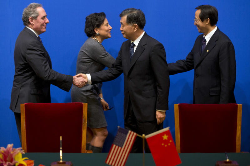 U.S. Trade Representative Michael Froman, left, and U.S. Secretary of Commerce Penny Pritzker, second left, shake hands with Chinese Vice Premier Wang Yang, second right, and Chinese Agricultural Minister Han Changfu, respectively, after Chinese and U.S. officials signed agreements at the 24th China-U.S. Joint Commission on Commerce and Trade held at Diaoyutai State Guesthouse in Beijing, Friday, Dec. 20, 2013. (AP Photo/Alexander F. Yuan, Pool)