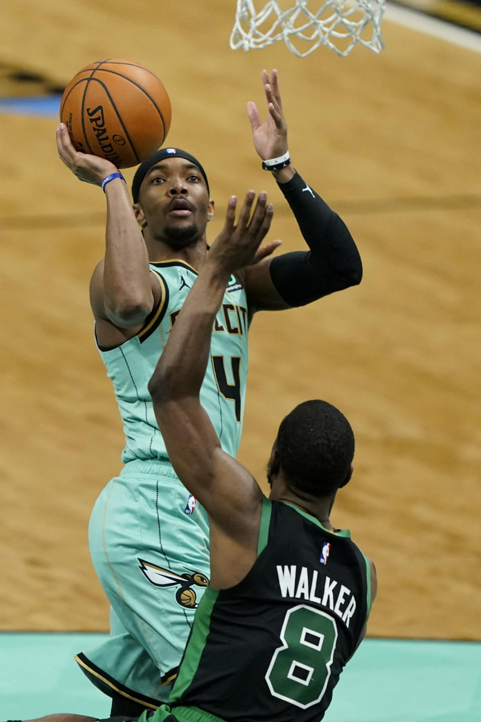 Charlotte Hornets guard Devonte' Graham shoots over Boston Celtics guard Kemba Walker during the first half of an NBA basketball game on Sunday, April 25, 2021, in Charlotte, N.C. (AP Photo/Chris Carlson)