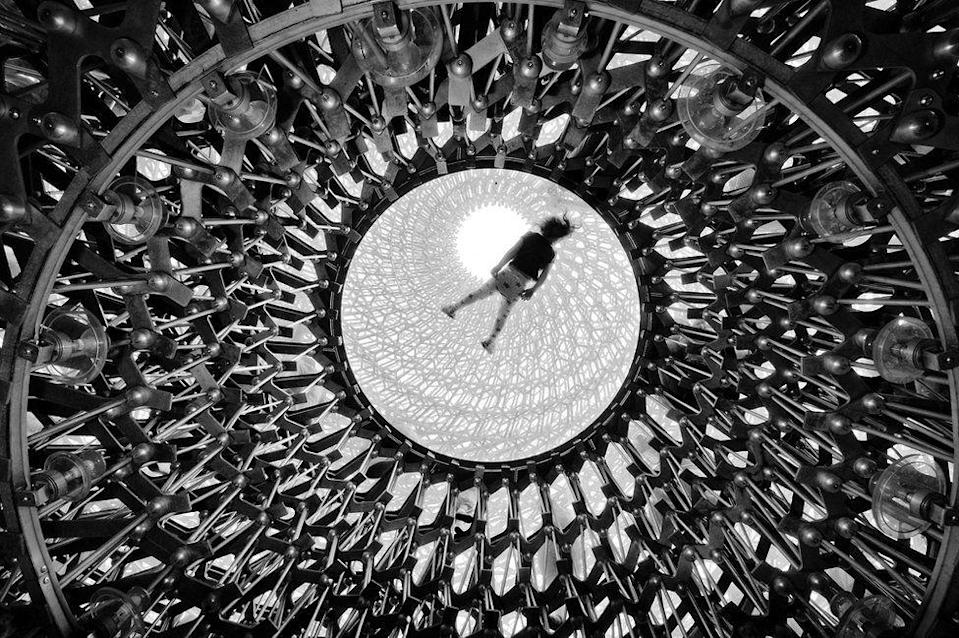 <p>Kew Gardens' 'Hive' installation is seen from below, as a visitor lies on the top glass platform. (Naf Selmani) </p>