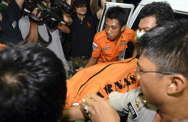 Indonesian rescue team members carry the body of the victim that a national rescue team said was a Japanese diver, to morgue in Bali, Indonesia, Tuesday, Feb. 18, 2014. Seven Japanese scuba divers who had been missing off Indonesia's resort island of Bali since last week. Five were found alive Monday, police said. (AP Photo/Firdia Lisnawati)