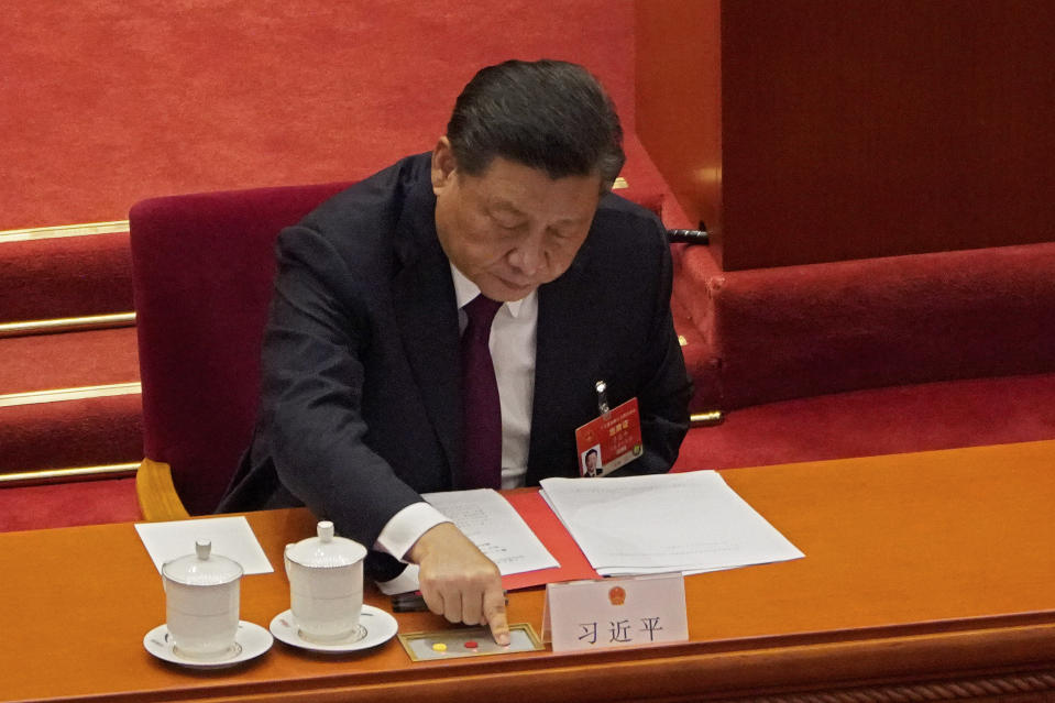 President Xi Jinping casts his vote during the closing session of the National People's Congress (NPC) at the Great Hall of the People in Beijing, Thursday, March 11, 2021. China's ceremonial legislature on Thursday endorsed the ruling Communist Party's latest move to tighten control over Hong Kong by reducing the role of its public in picking the territory's leaders. (AP Photo/Sam McNeil)