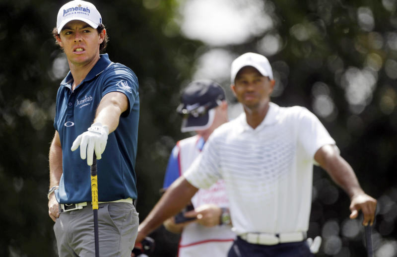 Rory McIlroy, left, of Northern Ireland, waits to tee off on the second hole as Tiger Woods watches during first round of play in the Tour Championship golf tournament in Atlanta on Thursday, Sept. 20, 2012. (AP Photo/John Bazemore)
