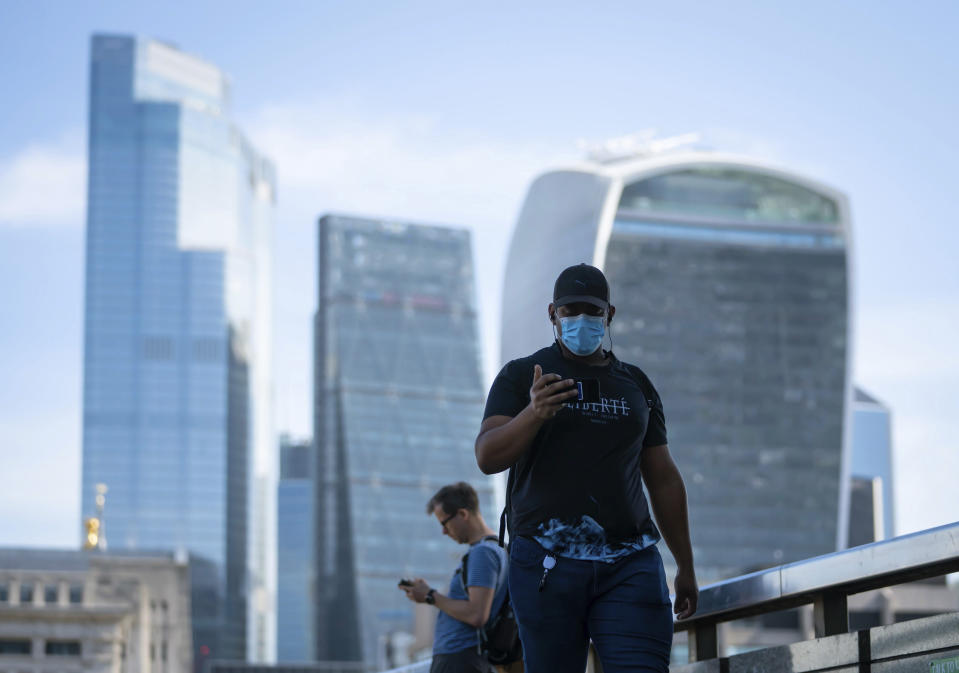 People commute on London Bridge during the morning rush hour after the introduction of measures to bring the country out of lockdown amid the coronavirus pandemic, in London, Wednesday May 20, 2020. (Dominic Lipinski/PA via AP)