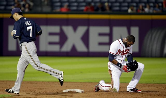 Atlanta Braves' Jason Heyward, right, kneels at second base after getting called out on a double play off a hit by teammate Jordan Schafer as Milwaukee Brewers' Norichika Aoki, of Japan, left, returns to dugout in the eighth inning of a baseball game, Monday, Sept. 23, 2013, in Atlanta. (AP Photo/David Goldman)