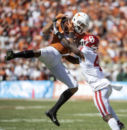 Texas wide receiver Collin Johnson makes a catch as Oklahoma cornerback Jaden Davis (4) defends in the second half of an NCAA college football game at the Cotton Bowl, Saturday, Oct. 12, 2019, in Dallas. Oklahoma won 34-27. (AP Photo/Jeffrey McWhorter)