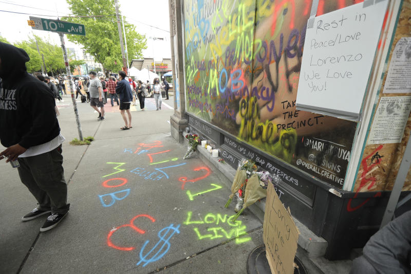"A sign that reads ""Rest in Peace/Love Lorenzo,"" is displayed at a growing memorial, Saturday, June 20, 2020, at the intersection of 10th Ave. and Pine St. near the Capitol Hill Occupied Protest zone in Seattle. A pre-dawn shooting near the area left one person dead and critically injured another person, authorities said Saturday. The area has been occupied by protesters after Seattle Police pulled back from several blocks of the city's Capitol Hill neighborhood near the Police Department's East Precinct building. (AP Photo/Ted S. Warren)"