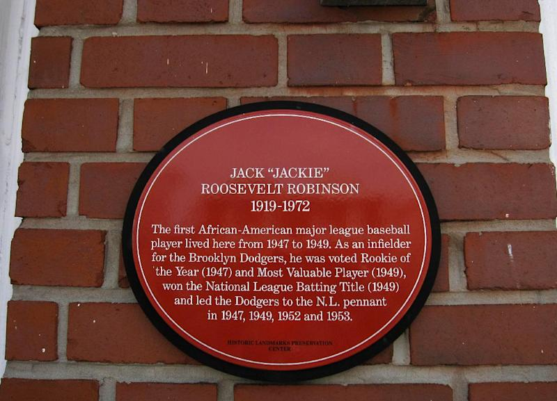 "This April 7, 2013 photo shows a plaque on a house in the Brooklyn borough of New York, where baseball great Jackie Robinson once lived. The sign says: ""The first African-American major league baseball player lived here from 1947 to 1949."" A new movie, ""42,"" tells Robinson's inspiring story as the man who integrated Major League Baseball. The house at 5224 Tilden Ave. in East Flatbush is one of a number of places in Brooklyn connected to Robinson. (AP Photo/Beth J. Harpaz)"