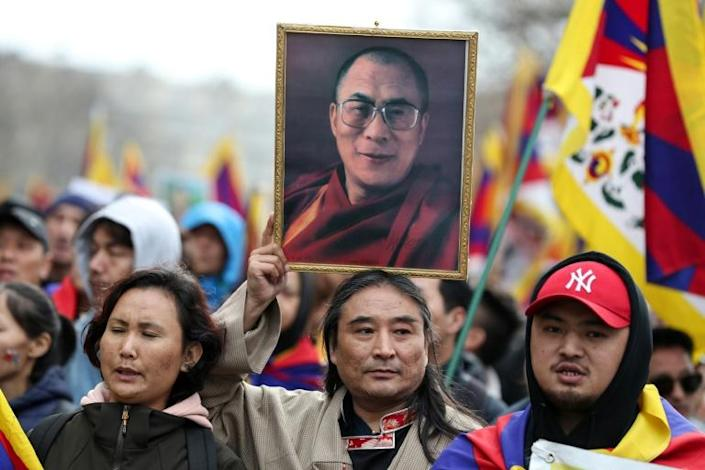 A supporter holds a portrait of Tibet's spiritual leader the Dalai Lama in Paris in March 2019 ahead of a visit by Chinese President Xi Jinping (AFP Photo/KENZO TRIBOUILLARD)