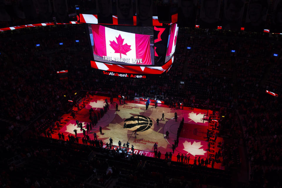 FILE - In this April 16, 2019, file photo, fans sing the Canadian national anthem before Game 2 of an NBA basketball first-round playoff series between the Orlando Magic and the Toronto Raptors in Toronto. The Canadian government has denied a request by the NBA and the Raptors to play in Toronto amid the pandemic. An official familiar with the federal government's decision told The Associated Press on Friday, Nov. 20, 2020, there is too much COVID-19 circulating in the United States to allow for cross-border travel that is not essential. (Nathan Denette/The Canadian Press via AP, File)