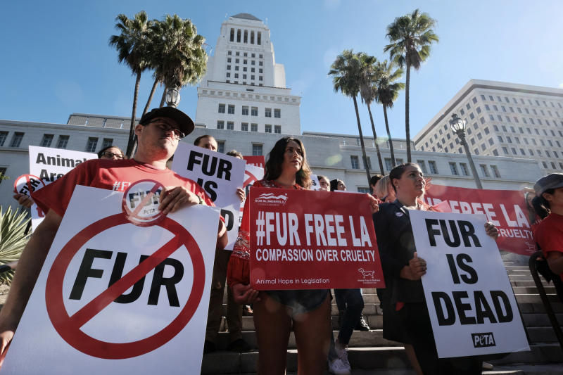 FILE -- In this Sept. 18, 2018 file photo protesters with the People for the Ethical Treatment of Animals (PETA) hold signs to ban fur in Los Angeles prior to a news conference at Los Angeles City.  California will ban the sale and manufacture of new fur products and bar most animals from circus performances under a pair of bills signed Saturday, Oct. 12, 2019 by Gov. Gavin Newsom.  (AP Photo/Richard Vogel,File)