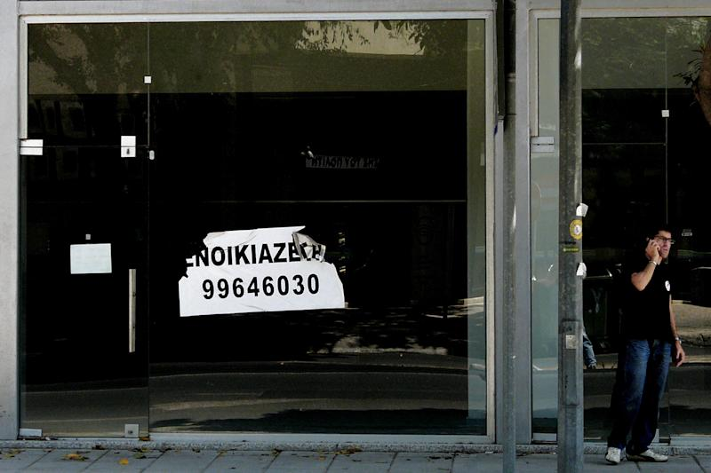 A man talks on his mobile phone outside an empty shop with a sign that reads in Greek: 'Rent' in central Nicosia, Cyprus, Tuesday, July 2, 2013. Moody's Investors Service said that it considers Cyprus to have defaulted after the debt-stricken island country swapped some local bonds for longer-term bonds. Cyprus negotiated a 23 billion euro ($30 billion) bailout with those entities in March. To get the money, Cyprus had to agree to cut spending and restructure its banking system. (AP Photo/Petros Karadjias)