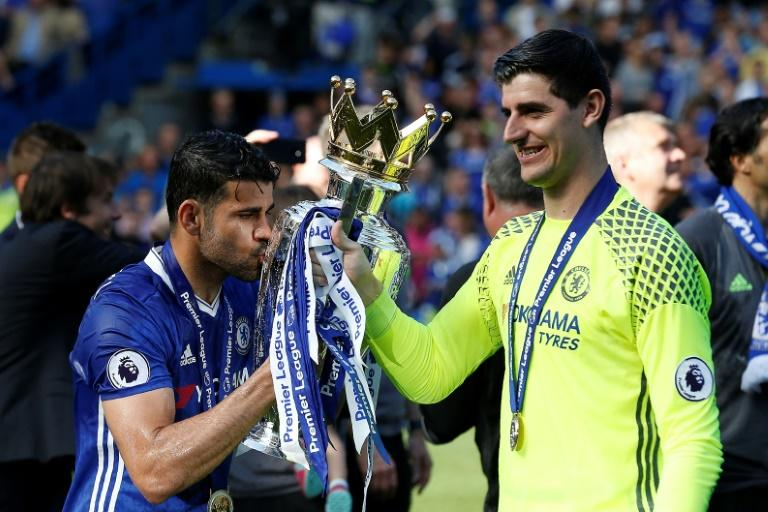 Chelsea's striker Diego Costa kisses the English Premier League trophy, held by Chelsea's goalkeeper Thibaut Courtois (R), as players celebrate their league title win at the end of the Premier League football match against Sunderland May 21, 2017