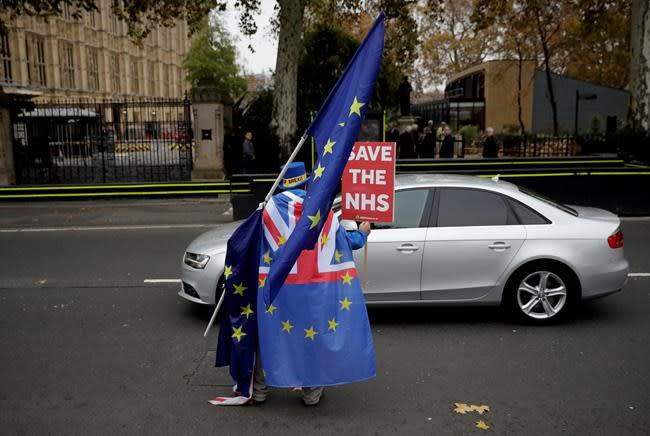 The Latest: UK's May vows 'to see this through' on Brexit