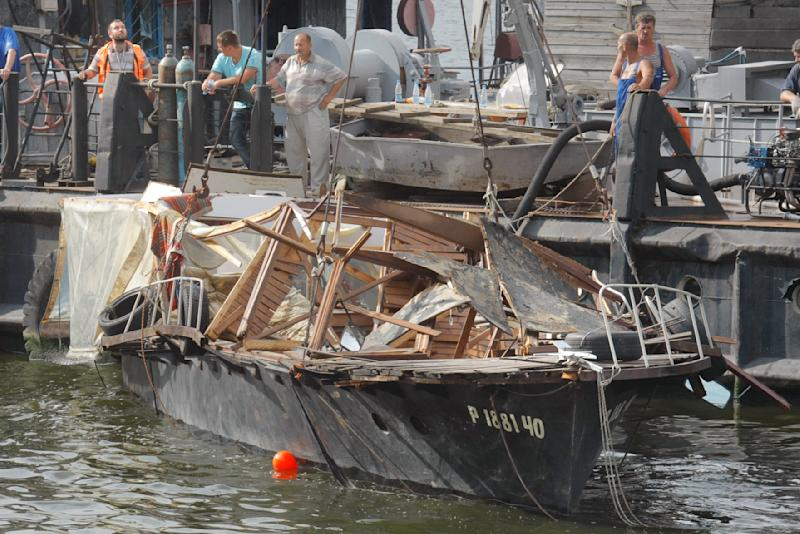 Russian emergency workers raise a pleasure boat that sank in Moscow, Russia, Sunday, July 31, 2011. Russian officials say an overloaded motor boat sank in the Moscow River after crashing into a docked barge in the pre-dawn darkness and 9 people were killed.  (AP Photo/Mikhail Metzel)