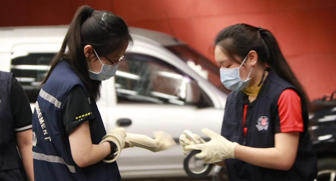 <p>Course participants from the CID prepare to process a 'crime scene' during the CID's Shooting Reconstruction Workshop. They must wear masks, gloves and shoe covers to avoid contaminating the crime scene.<br /> Photo: Hannah Teoh/Yahoo News Singapore </p>