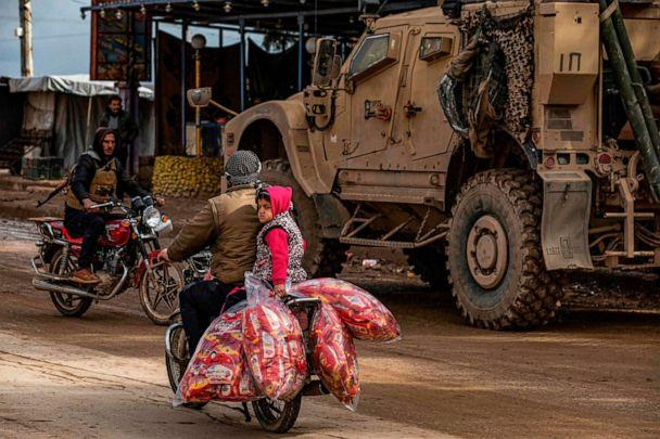 PHOTO: A man and a child ride a motorcycle loaded with bags of snacks as a patrol of U.S. military vehicles is seen in the town of Tal Tamr in the northeastern Syrian Hasakeh province along the border with Turkey on Feb. 8, 2020. (Delil Souleiman/AFP via Getty Images)