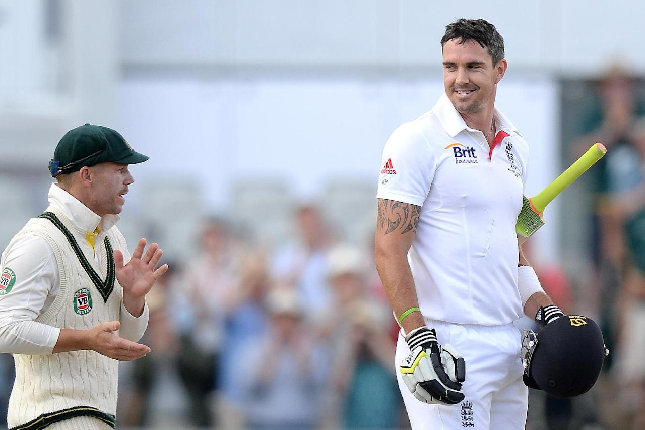 England's Kevin Pietersen celebrates his century with Australia's David Warner (left), during day three of the Third Investec Ashes test match at Old Trafford Cricket Ground, Manchester.