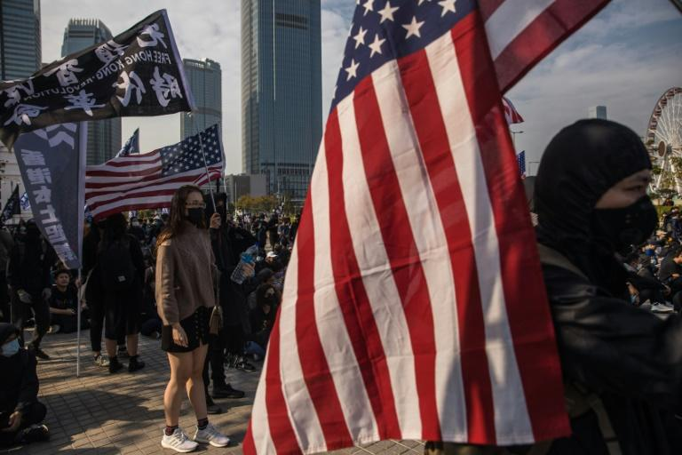 Pro-democracy protesters wave US flags during a rally in the Central district of Hong Kong on January 12, 2020 -- the same day the chief of US-based Human Rights Watch said he had been denied entry to the territory