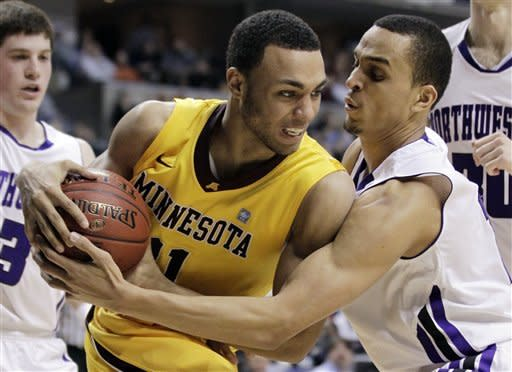 Minnesota guard Joe Coleman, front left, and Northwestern guard Reggie Hearn battle for the control of the ball in the overtime of an NCAA college basketball game at the first round of the Big Ten Conference tournament in Indianapolis, Thursday, March 8, 2012. (AP Photo/Michael Conroy)
