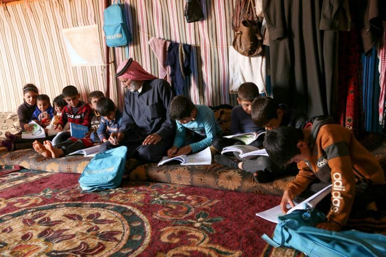 Syrian Abderrazaq Khatoun helps some of his 11 orphaned grandchildren with their school work inside a tent they call come in an encampment in the northwestern Syrian province of Idlib
