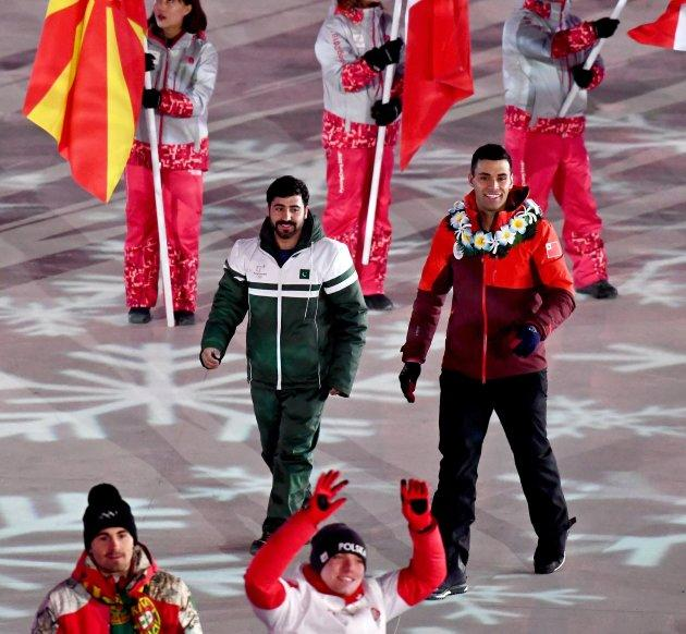 Pakistan's Muhammad Karim (L) and Tonga's Pita Taufatofua are photographed during the closing ceremony of the Pyeongchang 2018 Olympic Games in Pyeongchang county, South Korea, on Feb. 25, 2018.