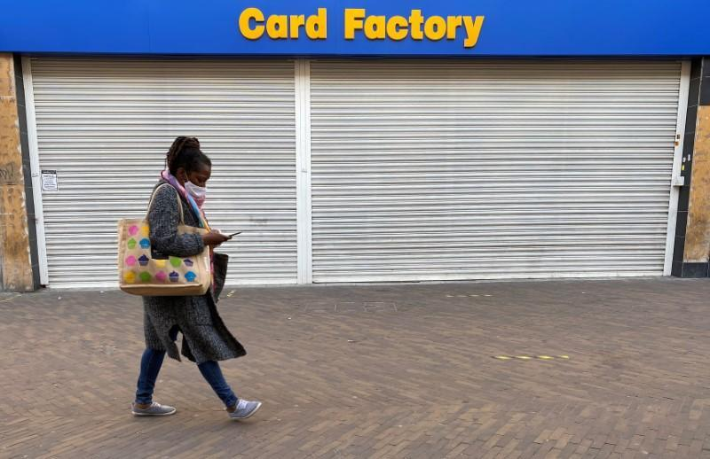 A woman wearing a face mask walks past a shuttered branch of Card Factory in Hackney, London