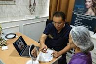 Thai surgeon Sakirin Al-Ishak explains the procedure to a patient waiting for plastic surgery in Bangkok