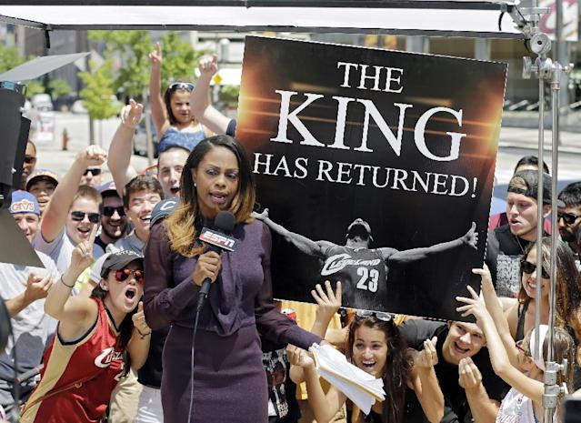 10ThingstoSeeSports - Fans cheer behind an ESPN reporter outside Quicken Loans Arena in Cleveland, after NBA basketball star LeBron James announced he would return to the Cleveland Cavaliers, Friday, July 11, 2014. (AP Photo/Mark Duncan, File)