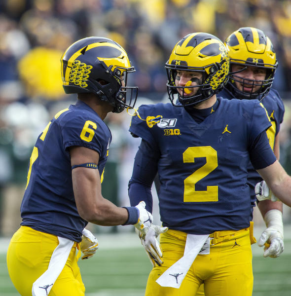 Michigan wide receiver Cornelius Johnson (6) celebrates his touchdown with quarterback Shea Patterson (2) in the fourth quarter of an NCAA college football game against Michigan State in Ann Arbor, Mich., Saturday, Nov. 16, 2019. Michigan won 44-10. (AP Photo/Tony Ding)