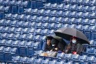 Philadelphia Phillies' fans watch the game as the rain falls during the fourth inning of a baseball game against the San Francisco Giants, Wednesday, April 21, 2021, in Philadelphia. (AP Photo/Chris Szagola)