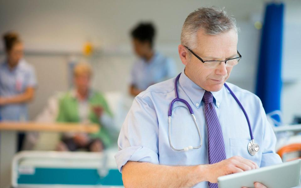 Doctor checking patient notes - Sturti/Getty