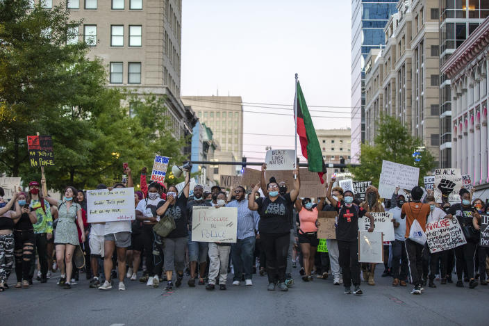 Protesters walk down Main Street in Lexington, Ky., during a rally against the deaths of George Floyd and Breonna Taylor on Sunday, May 31, 2020. (Ryan C. Hermens/Lexington Herald-Leader via AP)