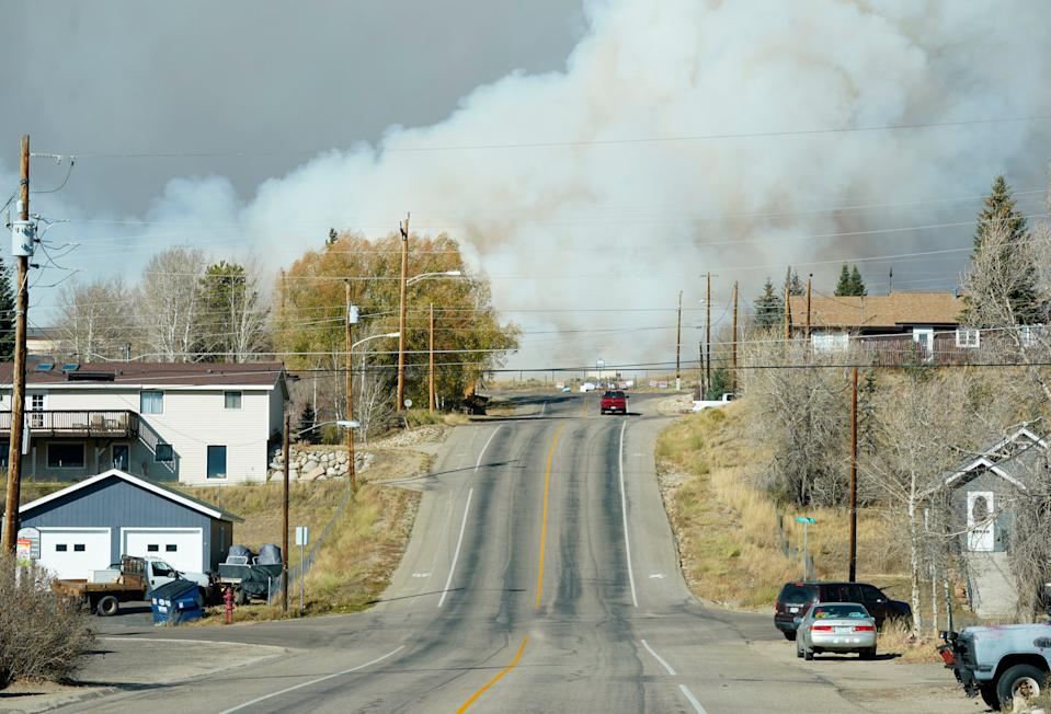 Smoke from wildfires rises in the background, Thursday, Oct. 22, near Granby, Colorado.