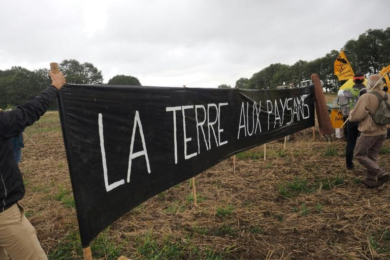 Waving the flag of France's Farmers' Confederation, they filled a seed drill with rye and sprayed grain in a demonstration they said symbolised the need to 'take back the land for the farmers'