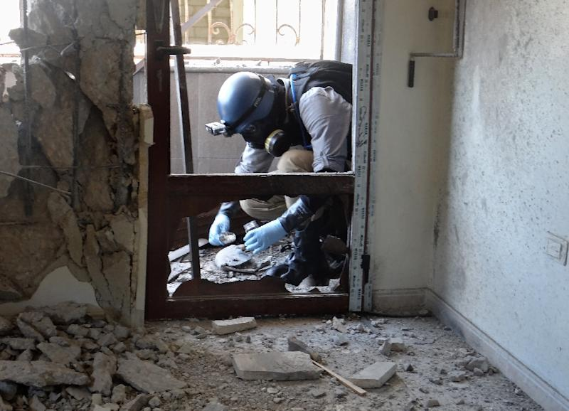 A United Nations weapons expert collects samples during an investigation into a 2013 suspected chemical weapons strike near Damascus
