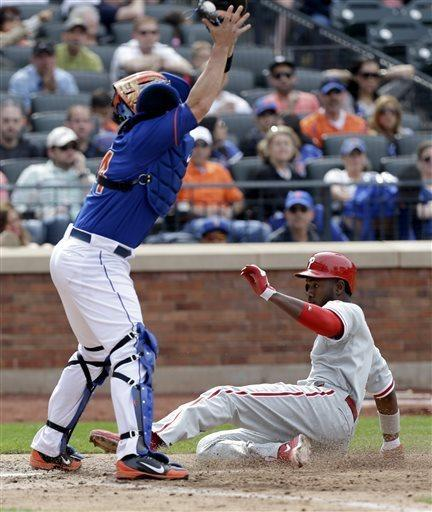 While New York Mets catcher John Buck, left, reaches up for the catch as Philadelphia Phillies' Domonic Brown slides safely home on a double hit by John Mayberry Jr. during the eighth inning of a baseball game at Citi Field, Sunday, April 28, 2013, in New York. (AP Photo/Seth Wenig)