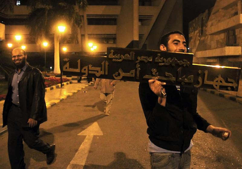 "An Egyptian man, right, carries a sign that reads in Arabic:""Arab Republic of Egypt, State security investigation device,"" after protesters stormed the offices of the state security building headquarters in Cairo's northern Nasr City neighborhood, Egypt, Saturday, March 5, 2011. Three weeks after President Hosni Mubarak's ouster, Egyptians are turning their anger toward his internal security apparatus, storming the agency's main headquarters and other offices Saturday and seizing documents to keep them from being destroyed to hide evidence of human rights abuses. (AP Photo/Ahmed Ali)"