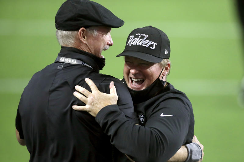 Las Vegas Raiders GM Mike Mayock, left, embraces head coach Jon Gruden after defeating the New Orleans Saints in an NFL football game, Monday, Sept. 21, 2020, in Las Vegas. (AP Photo/Isaac Brekken)