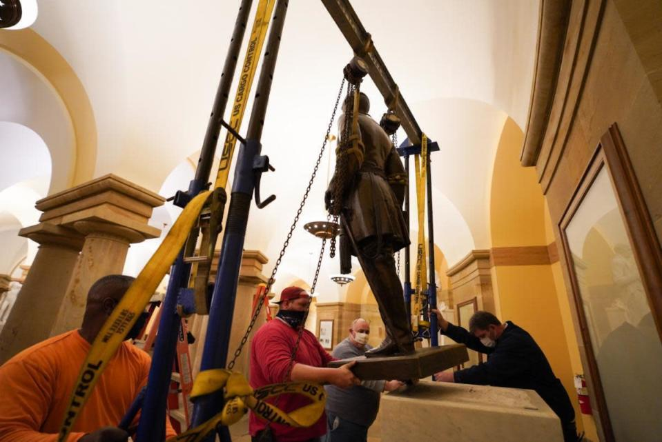 FILE - In this Dec. 21, 2020, file photo provided by the Office of the Governor of Virginia shows workers removing a statue of Confederate Gen. Robert E. Lee from the National Statuary Hall Collection in Washington. The statue that represented Virginia in the U.S. Capitol for 111 years was removed after a state commission decided that Lee was not a fitting symbol for the state. (Jack Mayer/Office of Governor of Virginia, File)