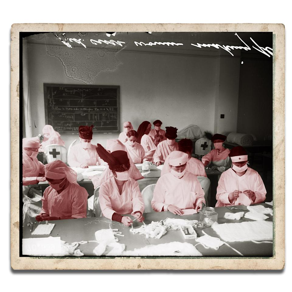 Red Cross Women sit at long tables making influenza masks in Chicago, Illinois in 1918.