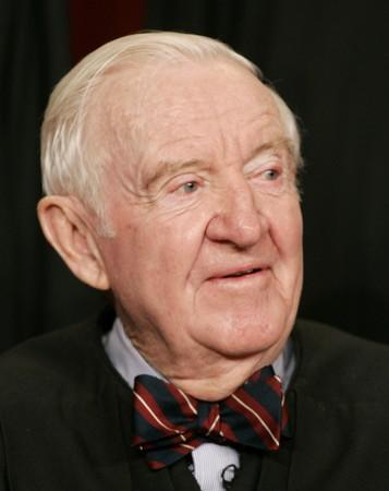 FILE PHOTO:  Justice John Paul Stevens sits as Justices of the Supreme Court of the United States pose for a 2006..
